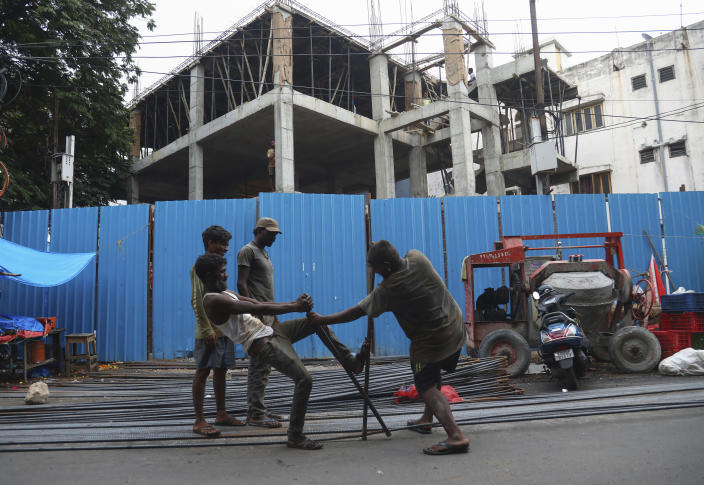 Laborers work at a construction site in Hyderabad, India, Friday, June 11, 2021. India's economy was on the cusp of recovery from the first pandemic shock when a new wave of infections swept the country, infecting millions, killing hundreds of thousands and forcing many people to stay home. Cases are now tapering off, but prospects for many Indians are drastically worse as salaried jobs vanish, incomes shrink and inequality is rising. (AP Photo/Mahesh Kumar A.)