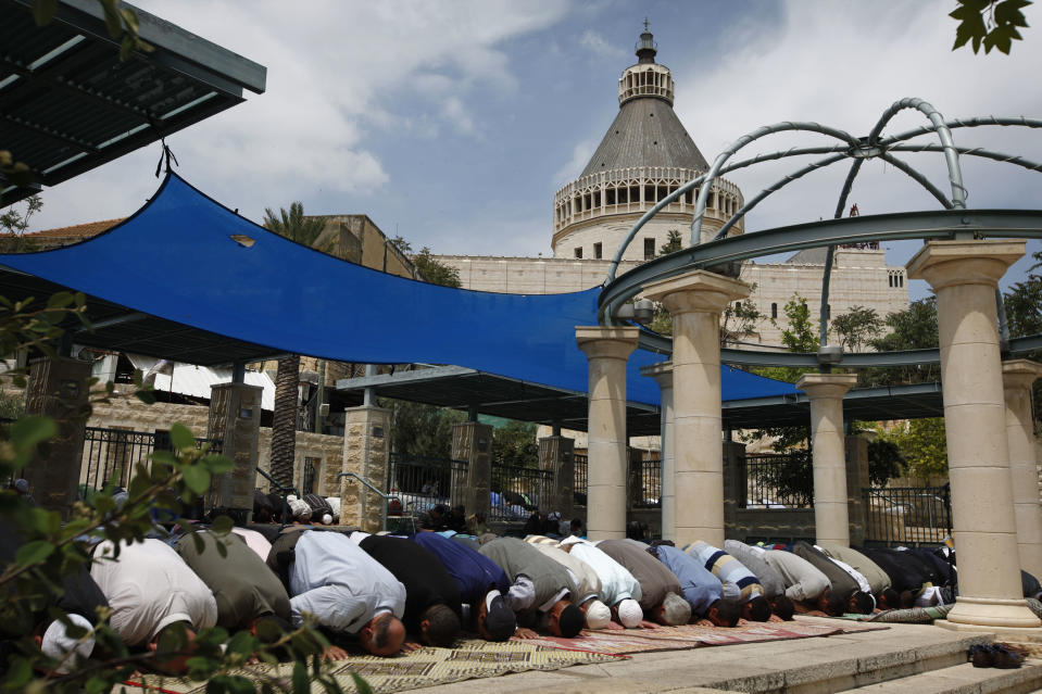 FILE - In this Friday, May 8, 2009 file photo, the Church of Annunciation, one of Christianity's holiest sites, is seen in the background as Israeli Arab Muslim worshippers pray during Friday noon prayers in the northern Israeli city of Nazareth. Texas A&M University said it plans on opening a branch campus in Israel, a first-of-its-kind project that will expand the American university's growing overseas presence. Texas A&M's chancellor, John Sharp, said Tuesday, Oct. 22, 2013, that the city, which is best known for being the place of Jesus' childhood, was chosen to help bring Israel's Arabs and Jews together in a center of learning. (AP Photo/Tara Todras-Whitehill, File)