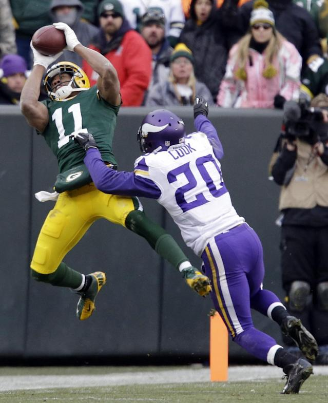 Green Bay Packers' Jarrett Boykin (11) catches a pass in front of Minnesota Vikings' Chris Cook (20) during the second half of an NFL football game Sunday, Nov. 24, 2013, in Green Bay, Wis. The game ended in a tie, 26-26. (AP Photo/Jeffrey Phelps)