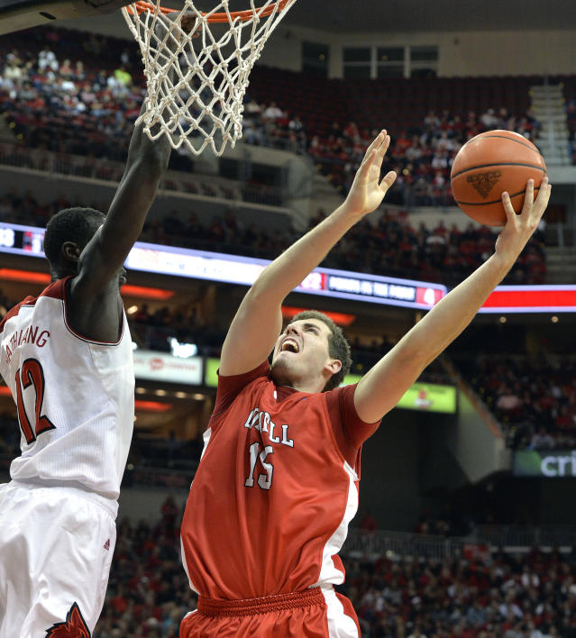 Cornell's Braxston Bunce, right, attempts a shot over the defense of Louisville's Mangok Mathiang during the first half of an NCAA college basketball game on Friday, Nov. 15, 2013, in Louisville, Ky. (AP Photo/Timothy D. Easley)