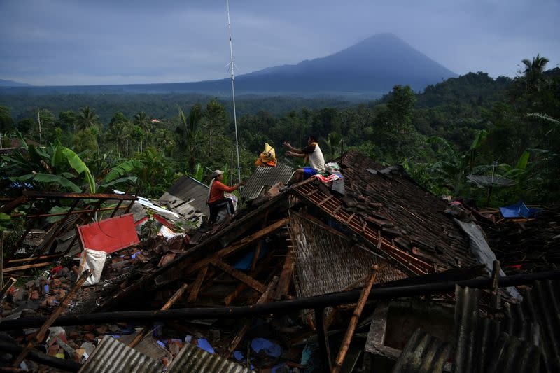 People salvage their belongings from a house damaged by an earthquake in Lumajang