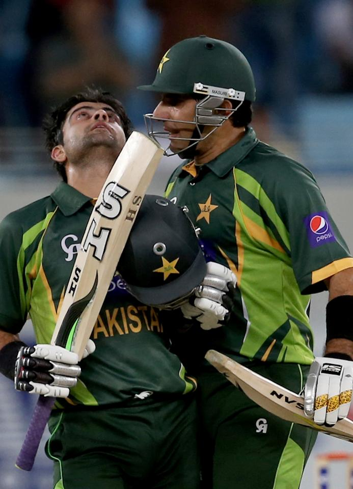 DUBAI, UNITED ARAB EMIRATES - DECEMBER 20:  Ahmed Shhzad (L) celebrates his century with Misbah Ul Haq (R) during the second One-Day International (ODI ) match between Sri Lanka and Pakistan at the Dubai Sports City Cricket Stadium on December 20, 2013 in Dubai, United Arab Emirates.  (Photo by Francois Nel/Getty Images)
