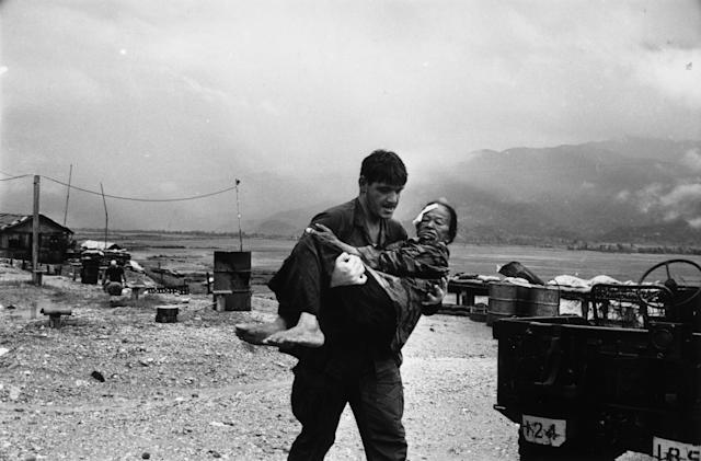 <p>A US soldier carrying a wounded refugee to safety during the war in Vietnam. (Photo: Terry Fincher/Daily Express/Hulton Archive/Getty Images) </p>