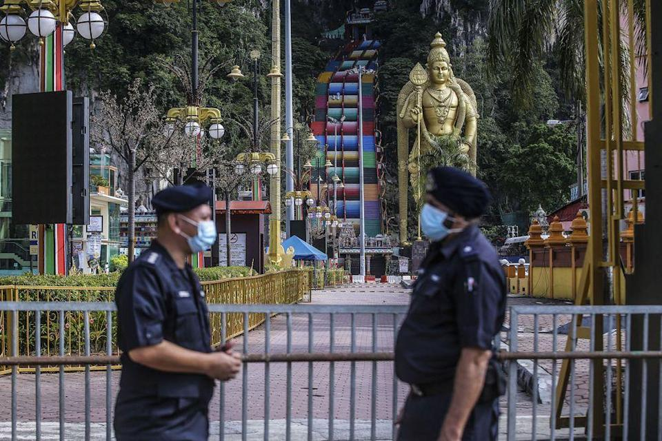 Police personnel stand guard in front of Batu Caves during Thaipusam January 28, 2021. — Picture by Hari Anggara