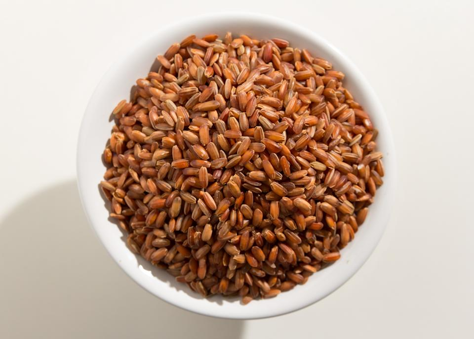 Oryza sativa is scientific name of Bhutanese Red Rice seed. Also known as Arroz Vemelho (portuguese). Top view of grains in a bowl. White background.