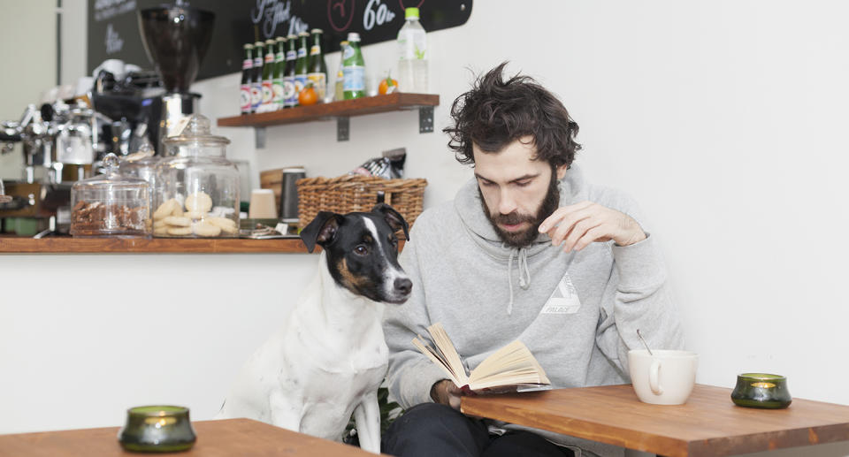 A man sits reading with a dog in a cafe.