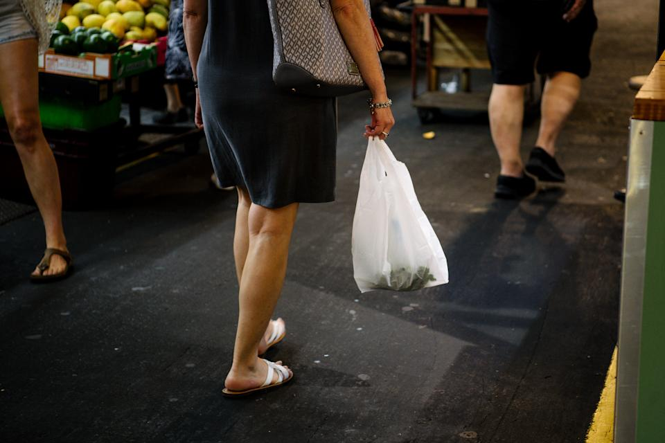 Pictured is a shopper carrying a single-use plastic bag