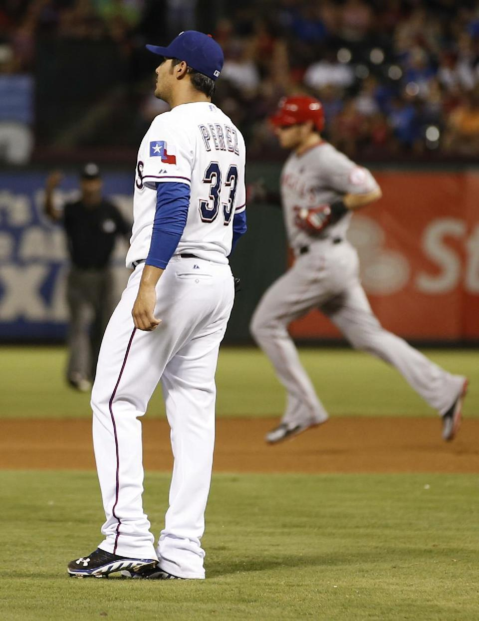 Texas Rangers starting pitcher Martin Perez (33) looks to the outfield as Los Angeles Angels' Josh Hamilton, right, rounds the bases after hitting a solo home run during the seventh inning of a baseball game, Wednesday, July 31, 2013, in Arlington, Texas. (AP Photo/Jim Cowsert)