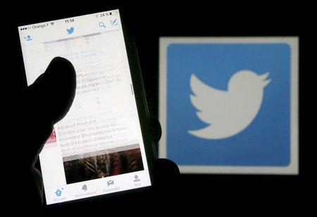 FILE PHOTO: A man reads tweets on his phone in front of a displayed Twitter logo in Bordeaux, southwestern France