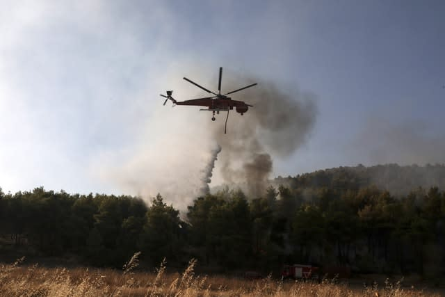 A helicopter operates over a wildfire in Makrymalli village