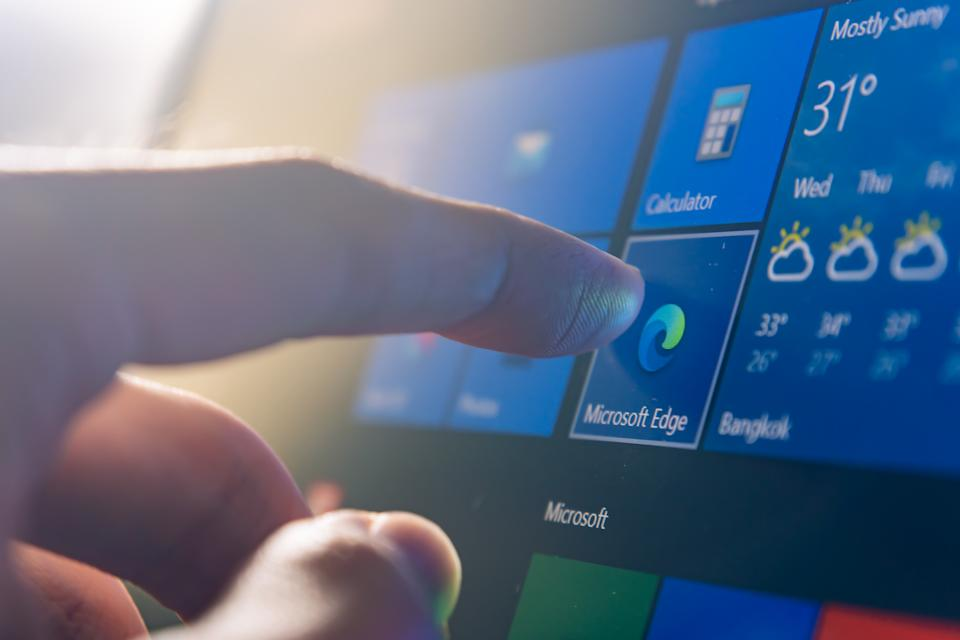 Bangkok, Thailand - August 20, 2020 : Computer user touching on Microsoft Edge, a web browser developed by Microsoft, icon on Windows 10 to open the program.