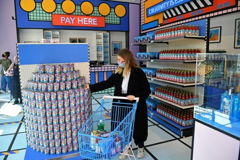 A worker fills a shopping cart with products designed by emerging artists inside the newly created High Street shop in the Design Museum in west London