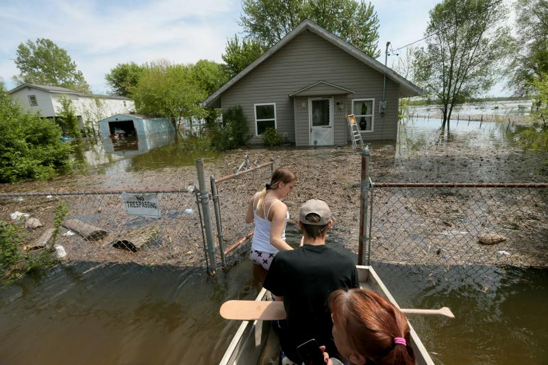 "Marissa Whitman, 20, wades in about 3 feet of floodwater from the swelling Mississippi River, while guiding a boat carrying her boyfriend Brendan Cameron and his mother, Tory Cameron, to their home along Pet Street, Sunday, May 5, 2019, in East Foley, Mo. ""I just need to see if the water reached inside,"" said Tory. The family had to evacuate Saturday when the water rose suddenly. (Laurie Skrivan/St. Louis Post-Dispatch via AP)"