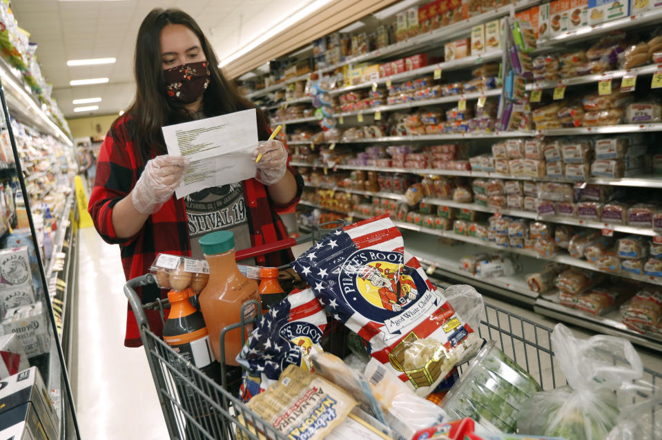 Alexandra Lopez-Djurovic checks her shopping list as she shops for a client in an Acme supermarket, Wednesday, July 1, 2020, in Bronxville, N.Y. (AP Photo/Kathy Willens)