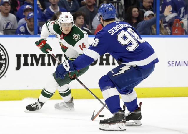 Minnesota Wild center Joel Eriksson Ek (14) moves around Tampa Bay Lightning defenseman Mikhail Sergachev (98) during the first period of an NHL hockey game Thursday, March 7, 2019, in Tampa, Fla. (AP Photo/Chris O'Meara)