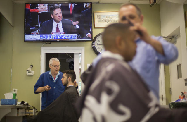 <p>Barbers cut hair for customers as televised coverage of former FBI director James Comey testifying is seen on television screen at Puglisi Hair Cuts in the Foggy Bottom neighborhood of Washington, June 8, 2017. (Pablo Martinez Monsivais/AP) </p>
