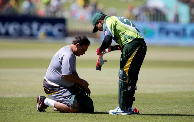 Kamran Akmal of Pakistan receives medical treatment on March 21, 2013 during the fourth one-day international against South Africa at Kingsmead in Durban.                  AFP PHOTO  / Stringer        (Photo credit should read -/AFP/Getty Images)