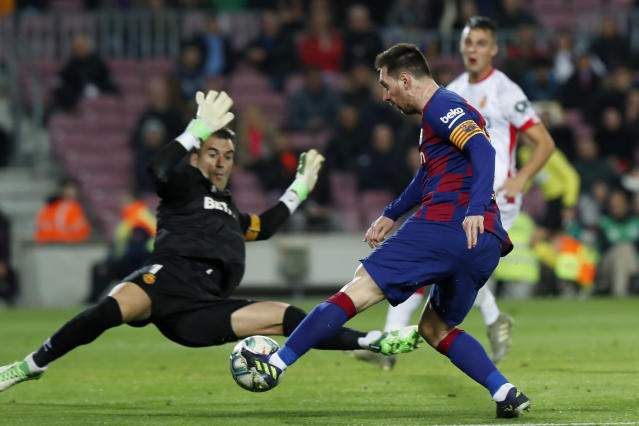 Barcelona's Lionel Messi attempts a shot at goal in front of Mallorca's goalkeeper Manolo Reina during a Spanish La Liga soccer match between Barcelona and Mallorca at Camp Nou stadium in Barcelona, Spain, Saturday, Dec. 7, 2019. (AP Photo/Joan Monfort)