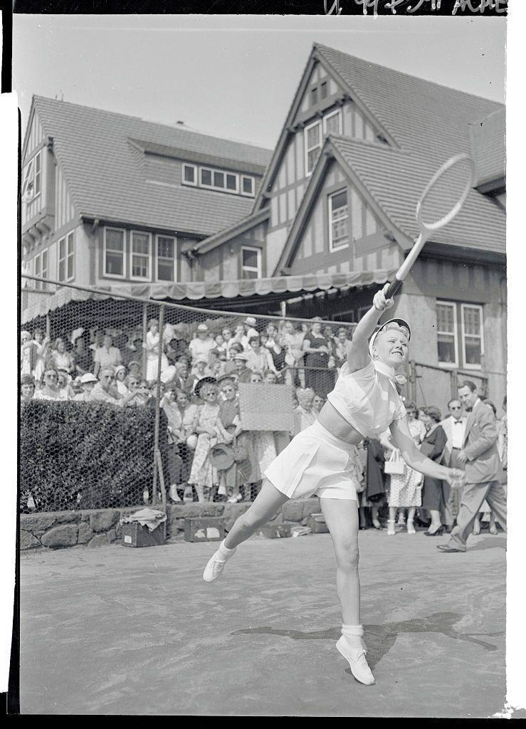 <p>Ginger Rogers hits the tennis court to practice for an upcoming mixed doubles match during the National Tennis Open Meet in 1950. </p>