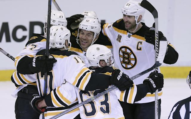 Boston Bruins right wing Jarome Iginla, center, is mobbed by teammates as they celebrate their 3-2 overtime win in Game 4 of a first-round NHL hockey playoff series against the Detroit Red Wings in Detroit, Thursday, April 24, 2014. Iginla was credited with the winning goal. (AP Photo/Carlos Osorio)