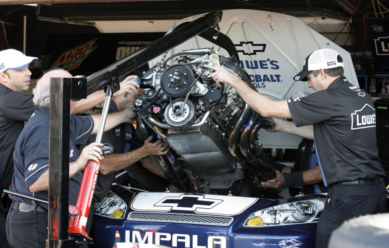 Crew members change the engine in Jimmie Johnson's car during morning practice for the NASCAR Pure Michigan 400 at Michigan International Speedway, Saturday, Aug. 18, 2012, in Brooklyn, Mich. (AP Photo/Dave Frechette)