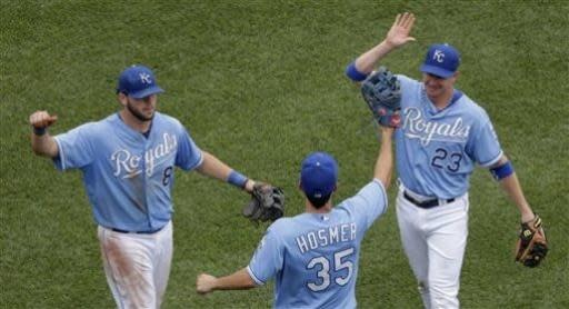 Kansas City Royals' Mike Moustakas (8), Eric Hosmer (35) and Elliot Johnson (23) celebrate after their baseball game against the Chicago White Sox, Sunday, June 23, 2013, in Kansas City, Mo. The Royals won 7-6. (AP Photo/Charlie Riedel)