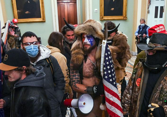 Jacob Anthony Chansley aka Jake Angeli aka the QAnon shaman wears face paint and horns in the Capitol on Jan. 6, 2021. He was later arrested and charged.