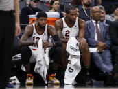 Los Angeles Clippers Paul George, left, and Kawhi Leonard, right, watch the closing moments of the Clippers 105-87 win over the Sacramento Kings in an NBA basketball game in Sacramento, Calif., Tuesday, Dec. 31, 2019. (AP Photo/Rich Pedroncelli)