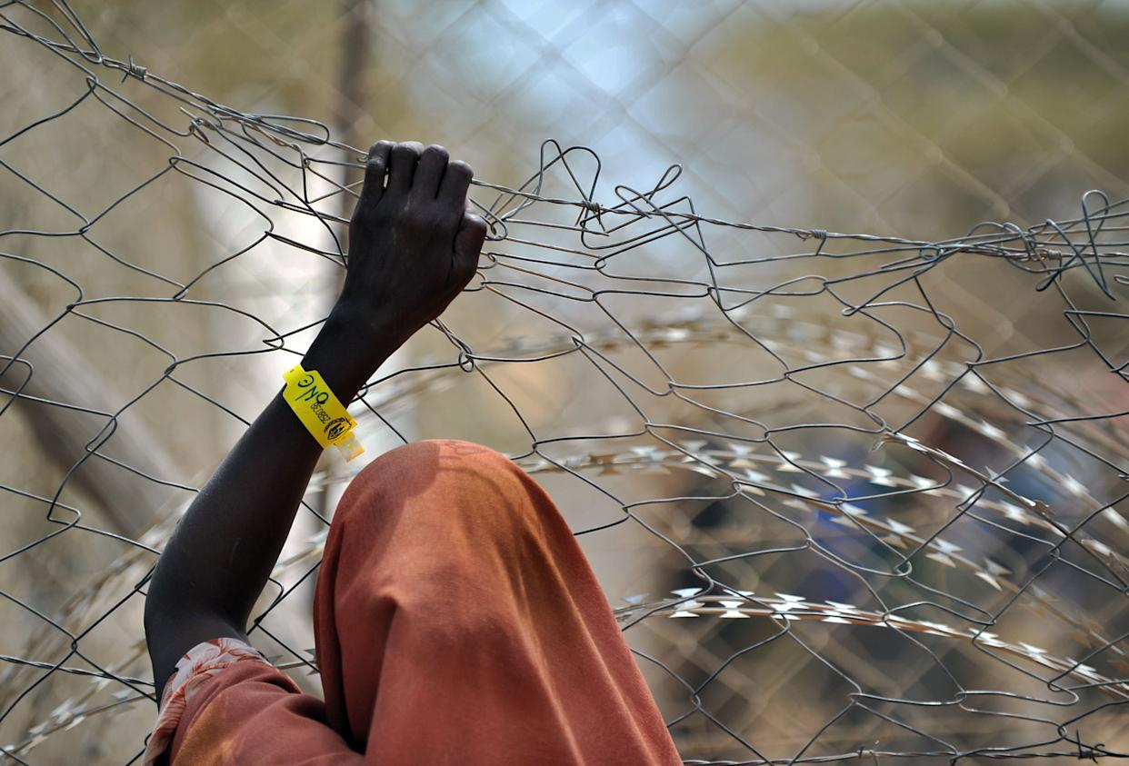 A newly registered Somali refugee supports herself on a chain-link perimeter fence outside a registration and medical aid facility at the Dadaab Internally Displaced People (IDP) camp in eastern Kenya on July 23, 2011 where the influx of Somali's displaced by a ravaging famine remains high.