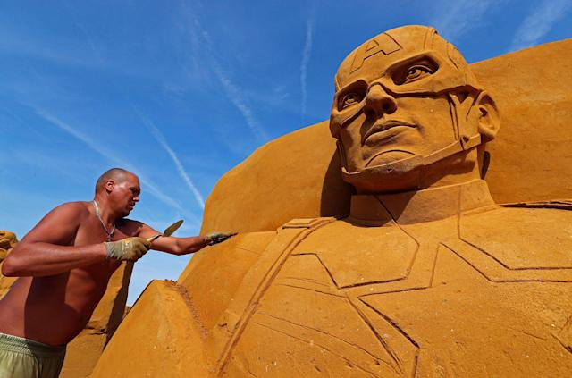 "<p>Sand carver Sergey Zaplatin from Russia works on a sculpture during the Sand Sculpture Festival ""Disney Sand Magic"" in Ostend, Belgium June 22, 2017. (Yves Herman/Reuters) </p>"