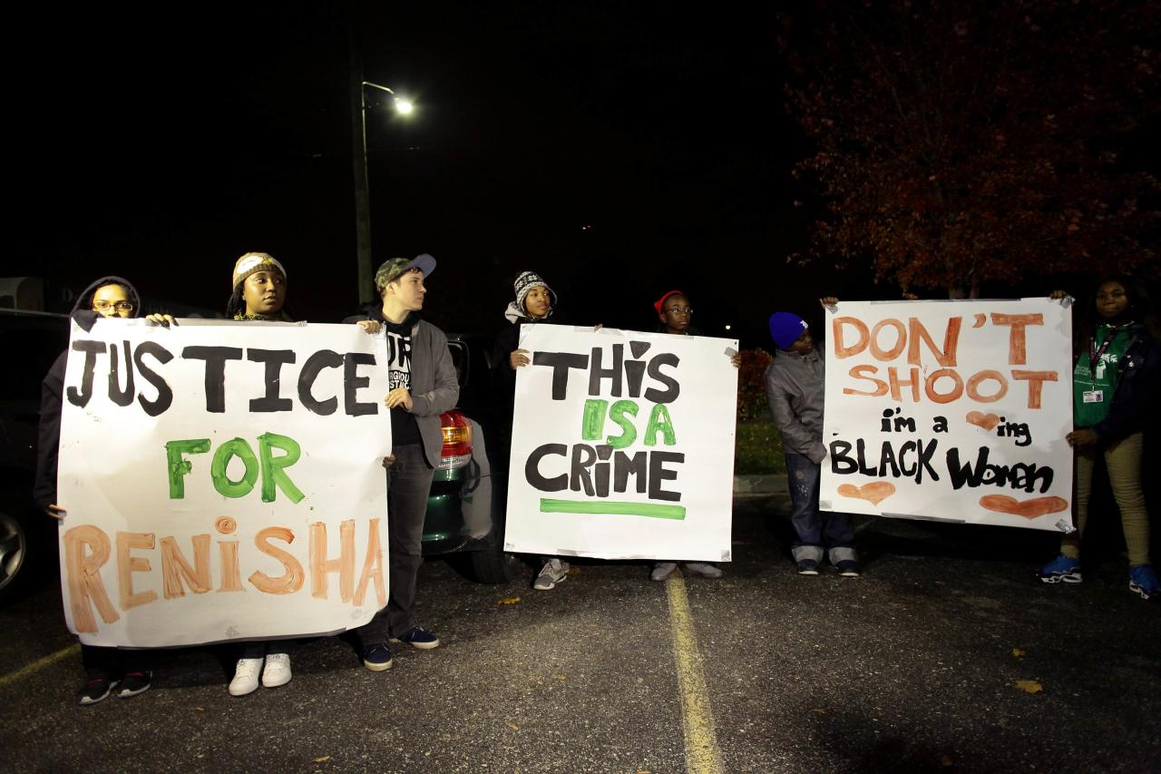 Demonstrators protest against the killing of 19-year-old Renisha McBride outside the Dearborn Heights Police Station in Dearborn Heights, Michigan November 7, 2013. McBride was killed by a homeowner's shotgun as she was seeking help after being involved in an automobile accident, according to activists and family members. They feel that McBride's killing last Saturday, which is still being investigated by authorities, was racially motivated. REUTERS/Joshua Lott (UNITED STATES - Tags: CRIME LAW)
