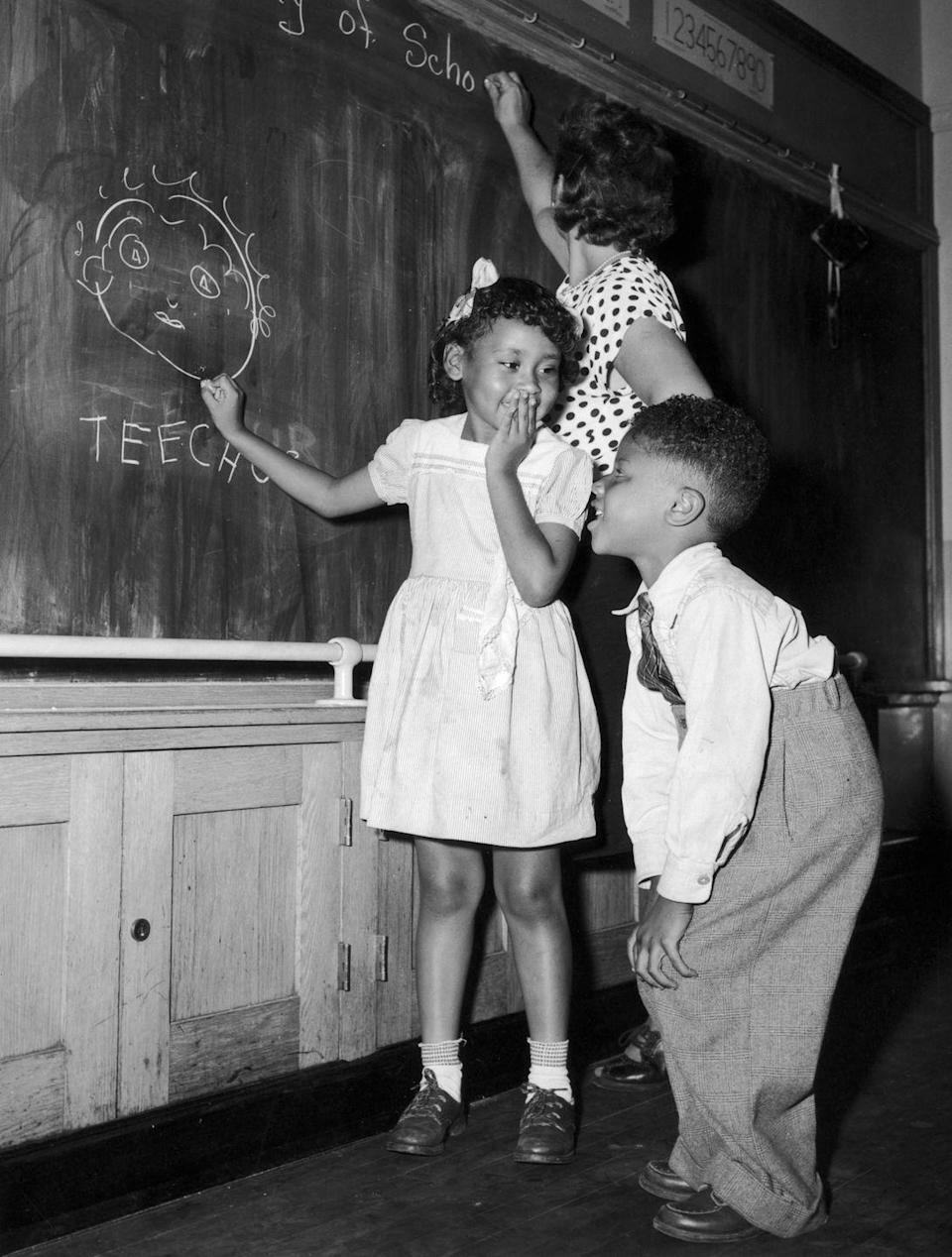 <p>Two students on their first day of school in Harlem, New York, have a little fun behind their teacher's back.</p>