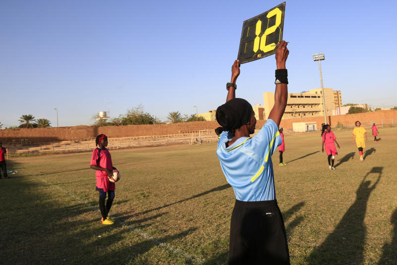 In this Wednesday, Dec. 11, 2019 photo, a referee holds a board as Sudanese al-Difaa, in pink, and al-Sumood women teams play in Omdurman, Khartoum's twin city, Sudan. The women's soccer league has become a field of contention as Sudan grapples with the transition from three decades of authoritarian rule that espoused a strict interpretation of Islamic Shariah law. (AP Photo)