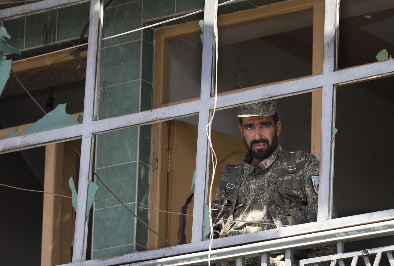 An Afghan Army soldier peers through a destroyed shop window at the scene where a suicide car bomber attacked a NATO convoy in Kabul, Afghanistan, Thursday, May 16, 2013. A Muslim militant group, Hizb-e-Islami, claimed responsibility for the early morning attack, killing many in the explosion and wounding tens, police and hospital officials said. The powerful explosion rattled buildings on the other side of Kabul and sent a pillar of white smoke into the sky in the city's east. (AP Photo/Anja Niedringhaus)