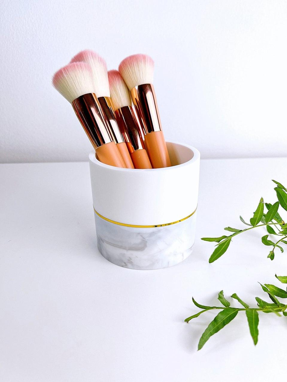 <p>If you have a sleek and modern aesthetic, the <span>White/Marble Makeup Brush Holder</span> ($22) will look fabulous on your vanity.</p>