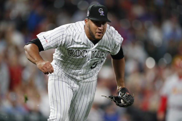 Colorado Rockies relief pitcher Carlos Estevez fields a ground ball off the bat of St. Louis Cardinals' Kolten Wong during the eighth inning of a baseball game Wednesday, Sept. 11, 2019, in Denver. (AP Photo/David Zalubowski)