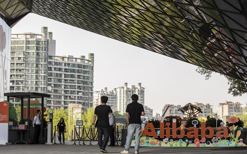 People walk past a sign at the Alibaba Group Holding Ltd. headquarters in Hangzhou, China - Qilai Shen/Bloomberg