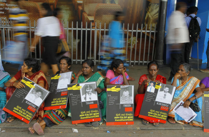 In this Monday, April 6, 2015, file photo, Sri Lankan ethnic Tamil women sit holding placards with portraits of their missing relatives as they protest outside a railway station in Colombo, Sri Lanka. Sri Lanka's president has decided that tens of thousands of people still missing from the country's quarter-century civil war will be formally declared dead and death certificates will be issued, his office said Monday. (AP Photo/Eranga Jayawardena)