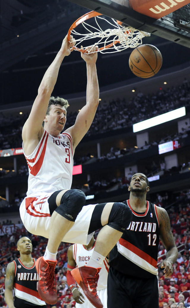 Houston Rockets' Omer Asik (3) dunks the ball over Portland Trail Blazers' LaMarcus Aldridge (12) in the second half of Game 5 of an opening-round NBA basketball playoff series Wednesday, April 30, 2014, in Houston. The Rockets won 108-98 to send the teams back to Portland for Game 6. (AP Photo/Pat Sullivan)