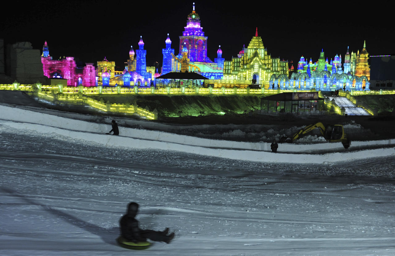 A visitor sleighs down a snow slope near ice sculptures during the lights testing period of the 13th Harbin Ice and Snow World in Harbin, Heilongjiang province December 25, 2011. The Harbin International Ice and Snow Festival will be officially launched on January 5, 2012. Picture taken December 25, 2011. REUTERS/Sheng Li (CHINA - Tags: ENVIRONMENT SOCIETY TRAVEL)