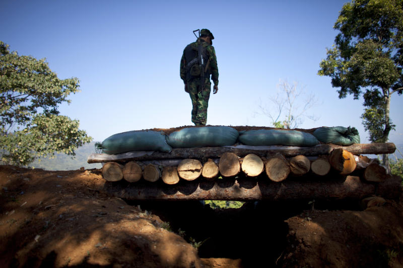 In this Jan. 31, 2013 photo, a Kachin Independence Army soldier stands on top of a bunker at an outpost on the Law Hpyu hilltop, one of the last hilltop outposts defending Laiza, where the guerrilla group's headquarters are located, in northern Myanmar's Kachin-controlled region. Kachin state is home to the last rebel insurgency left fighting in Myanmar that hasn't signed a cease-fire with President Thein Sein's government. Although the hills around Laiza have grown quiet for now, the dramatic upsurge in fighting underscored how far Myanmar is from achieving one of the things it needs most - a political settlement to end not just the war with the Kachin, but simmering conflicts with more than a dozen other rebel armies which have plagued the country for decades and still threaten its future. (AP Photo/Alexander F. Yuan)