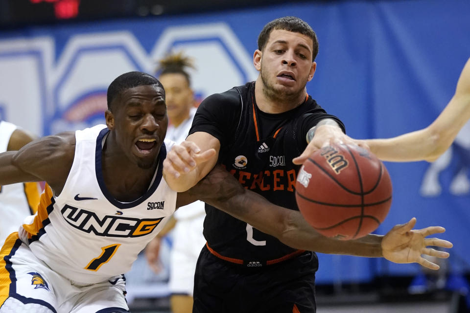 UNC-Greensboro guard Isaiah Miller (1) and Mercer guard Neftali Alvarez (2) reach for a loose ball in the first half of an NCAA men's college basketball championship game for the Southern Conference tournament, Monday, March 8, 2021, in Asheville, N.C. (AP Photo/Kathy Kmonicek)