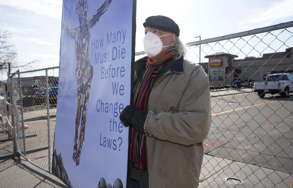 Stephen Parlota of Boulder, Colo., holds his handmade sign in front of a makeshift fence put up around the parking lot outside a King Soopers grocery store where a mass shooting took place Tuesday, March 23, 2021, in Boulder, Colo. (AP Photo/David Zalubowski)