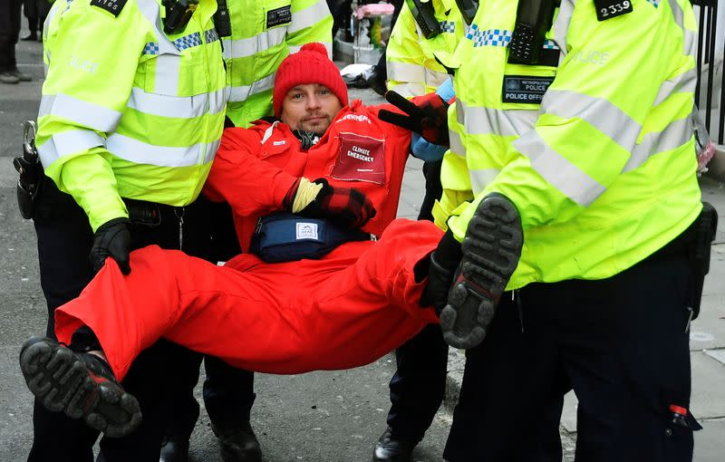 Greenpeace climate activist looks on as he is being removed by police officers near the entrance to BP's head office in London