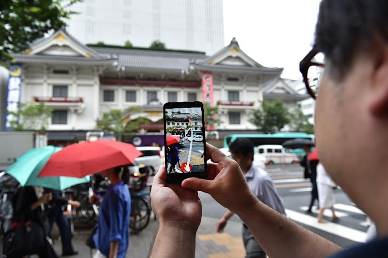 A man plays the Pokemon Go game on his mobile phone in front of the Kabukiza theater in Tokyo (AFP Photo/Kazuhiro Nogi)