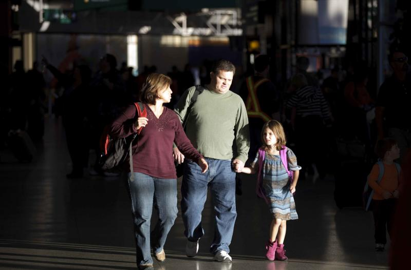 FILE - In this Nov. 22, 2011, file photo, a family arrives at the airport for a Thanksgiving holiday in San Diego. Airlines are making it much more difficult for groups of travelers to sit together, unless they want to pay extra for seats with more legroom or those near the front of the plane. Since last Thanksgiving, American Airlines, Delta, Frontier and United have increased the number of coach seats requiring an extra fee. That means it's much more difficult to find adjacent seats unless passengers pay an extra $25 per person, each way. (AP Photo/Gregory Bull, File)