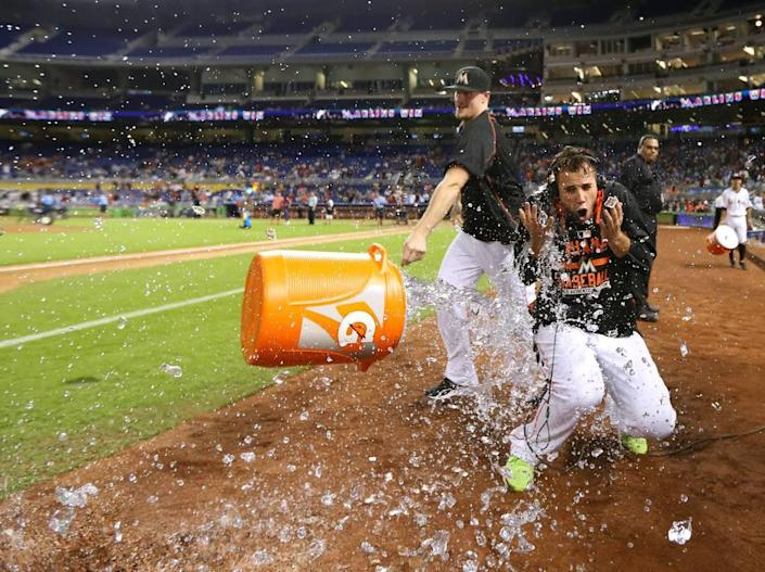 Tom Koehler, of the Miami Marlins, throws a cooler of ice water to teammate Jose Fernandez after the Marlins defeated the Atlanta Braves 12-11 on Friday, Sept. 25, 2015, at Marlins Park in Miami. Jose Fernandez became the first pitcher in the modern era to win his first 17 career home decisions.