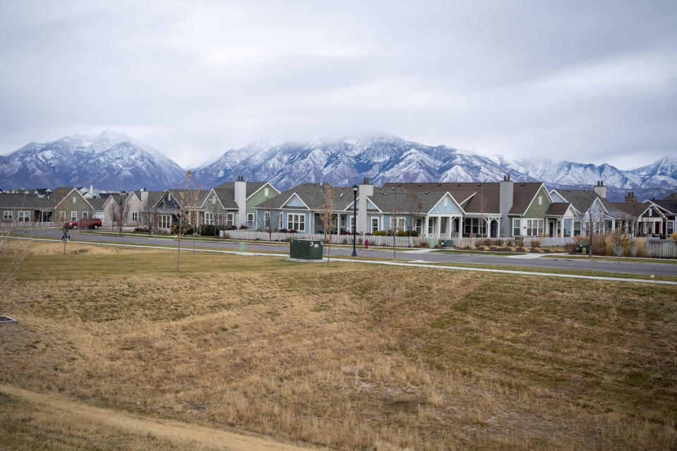Homes line up against the backdrop of snow capped mountains in South Jordan, Utah, Sunday, Nov. 15, 2020. Founded by believers in what was then a small, fringe religion, Utah was then lost in the desolation of mountains and deserts, and viewed with suspicion by much of America. The insularity that resulted has been fading over the past few decades, but it's still a place intensely proud of its own distinctiveness. (AP Photo/Wong Maye-E)