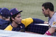 Milwaukee Brewers' Christian Yelich, left, talks to a teammate during the ninth inning of a baseball game against the Miami Marlins, Sunday, May 9, 2021, in Miami. (AP Photo/Marta Lavandier)