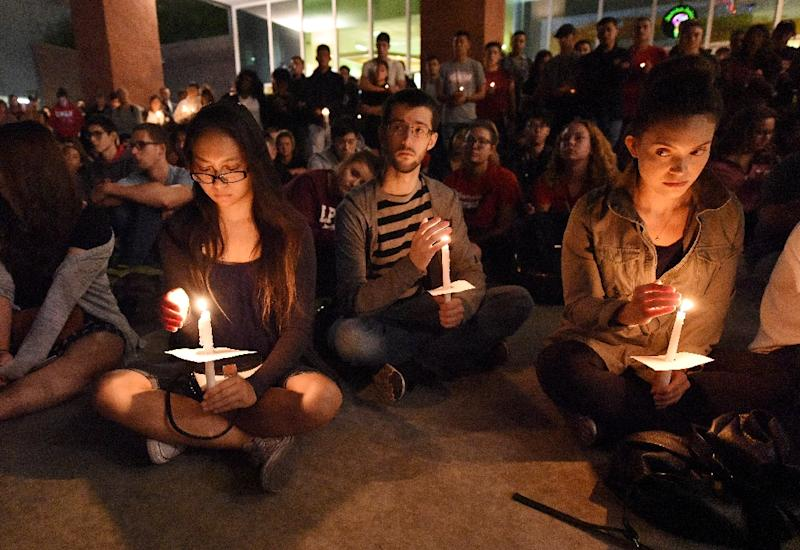 People attend a candlelight vigil at the University of Las Vegas student union the day after a gunman killed at least 58 people and wounded more than 500 others October 1